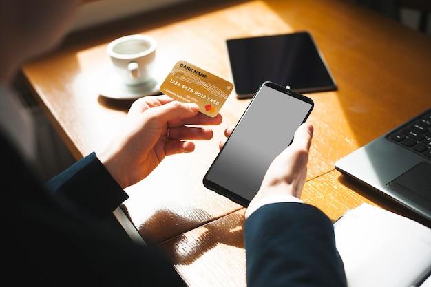 태블릿 및 노트북에서 일하는 커피 숍에 앉아있는 동안 골드 신용 카드와 스마트 폰을 사용하는 남성 손의 위보기.