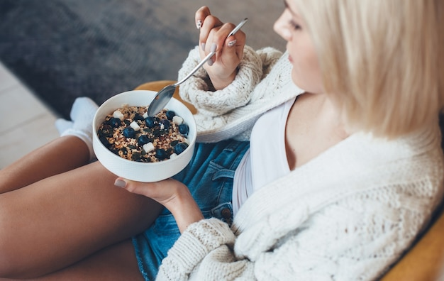 Upper view photo of a blonde caucasian woman eating cereals with fruits