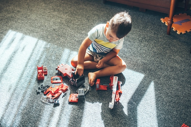 Upper view photo of a caucasian boy playing on the floor with constructor car and toys