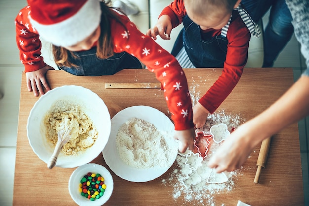 Upper view photo of children making cookies using flour and dough for christmas wearing santa clothes