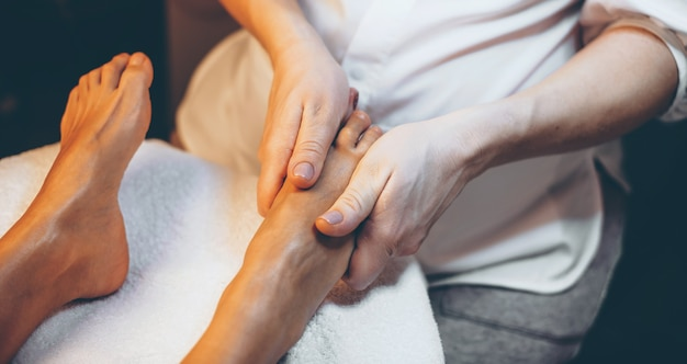 Upper view photo of a feet massage session at the spa salon done to a woman