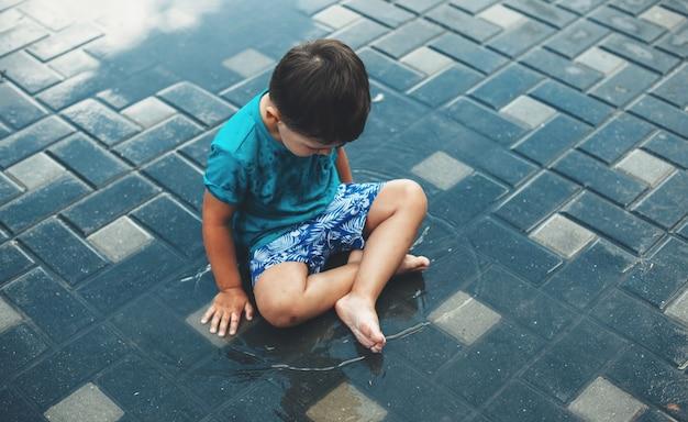 Фотография сверху кавказского мальчика, сидящего в воде на улице во время летних каникул