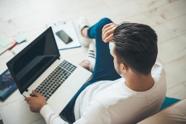 いくつかのドキュメントと床に空きスペースがあるコンピューターで働いている白人ビジネスマンの上面写真
