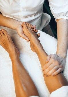 スパサロンでレッグマッサージセッションをしている白人女性の上面写真