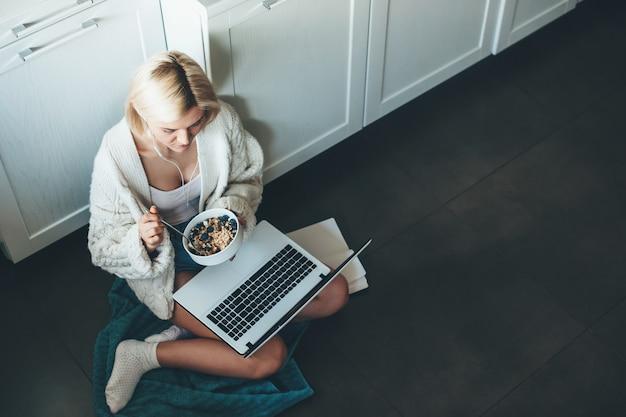 Фотография сверху: кавказская женщина со светлыми волосами и наушниками сидит на кухне на полу и ест за ноутбуком хлопья