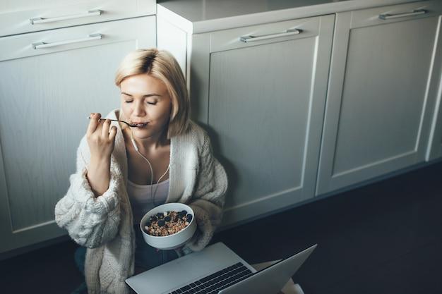 ノートパソコンを使用しながら床でシリアルを食べるダイエット金髪女性の上面写真