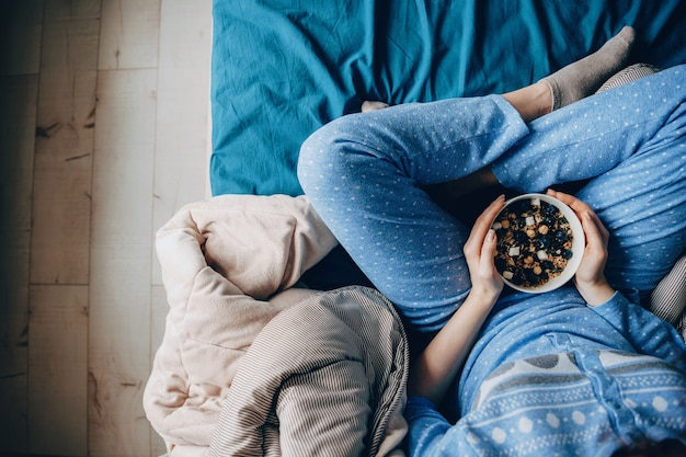 Фотография сверху: женщина в пижаме со здоровыми привычками ест злаки