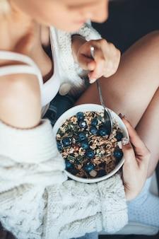 Фотография сверху женщины со здоровыми привычками, поедающей злаки с ягодами