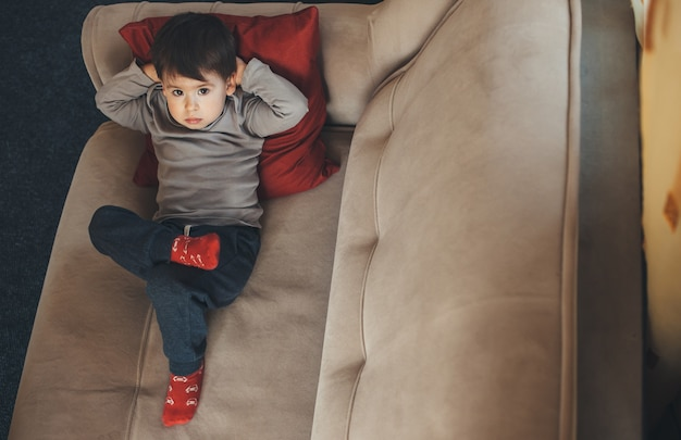Upper view portrait of a caucasian boy isolated in home during the quarantine lying on the sofa