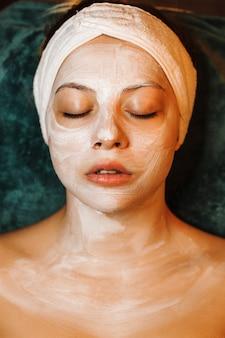 Верхний вид портрет удивительной кавказской женщины, опирающейся на спа-кровать с белой маской на лице с закрытыми глазами.