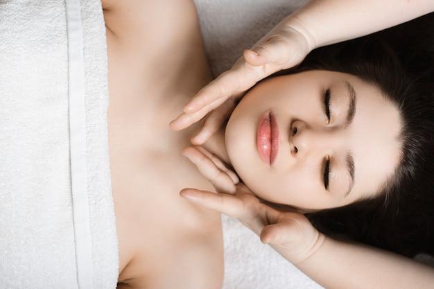 Верхний вид портрет красивой женщины, имеющей массаж лица перед тем, как делать маску в оздоровительном спа-центре.