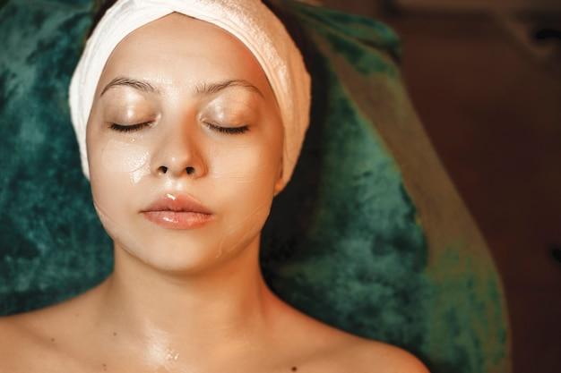 Верхний вид портрет красивой женщины, отдыхающей во время процедур по уходу за кожей на лице в спа-салоне.