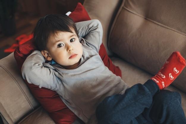 ソファで休んで、検疫中にカメラを見上げている白人の少年の上面図の肖像画