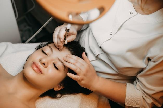 Портрет красивой женщины с неинвазивной микродермабразией на лице, лежащей на спа-кровати с закрытыми глазами.