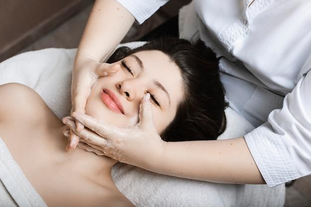Верхний вид портрет прекрасной молодой женщины, имеющей массаж лица косметологом в спа-центре.