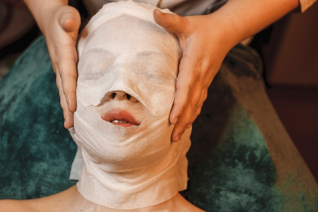 Upper view of a woman resting while having skin care routine in a spa salon.