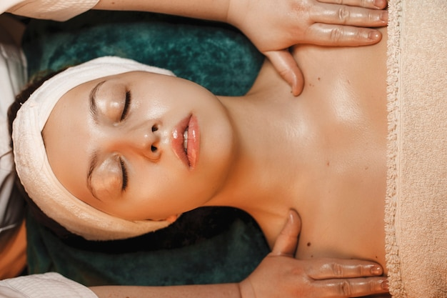 Upper view of a young woman doing skin care routine in welles spa salon.
