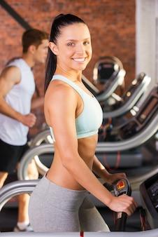 Увеличиваю кардио. вид сбоку красивой молодой женщины, идущей на беговой дорожке и улыбающейся с мужчиной на заднем плане