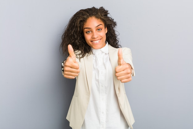 親指を持つ若いアフリカ系アメリカ人ビジネス女性ups、何かについての歓声、サポートおよび尊重の概念。
