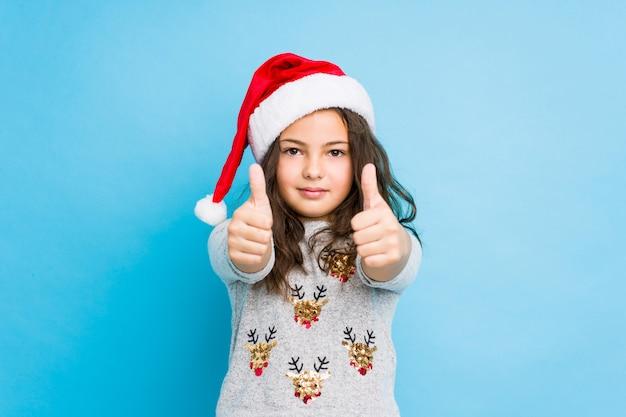 親指でクリスマスの日を祝う少女ups、何かについて乾杯、サポートと尊重の概念。