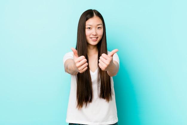 親指を持つ若いかなり中国人女性ups、何かについて歓声、サポートおよび尊重の概念。