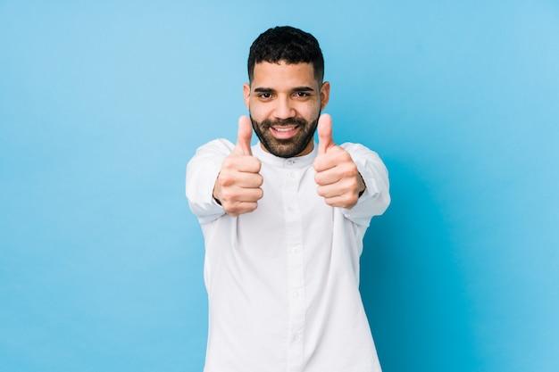 親指で分離された青い壁に若いラテン男ups、何かについての歓声、サポートおよび尊重の概念。