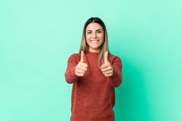 親指で分離された若い白人女性ups、何かについての歓声、サポートおよび尊重の概念。