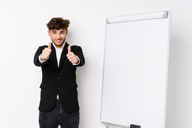 親指を持つ若いビジネスコーチング男ups、何かについて乾杯