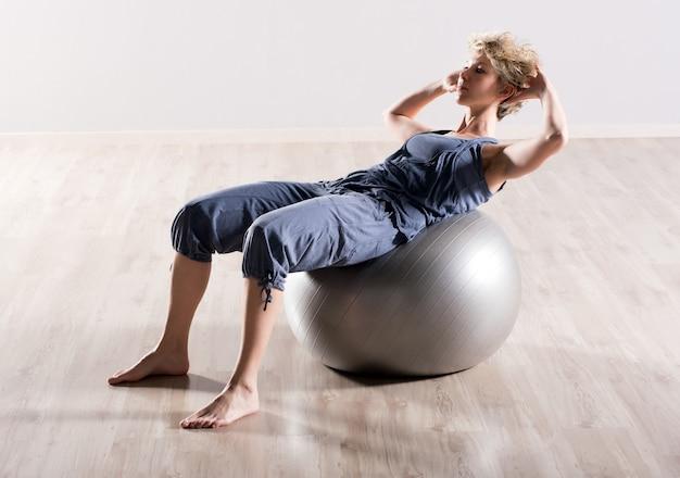 座る若い女性は安定性ボールにups