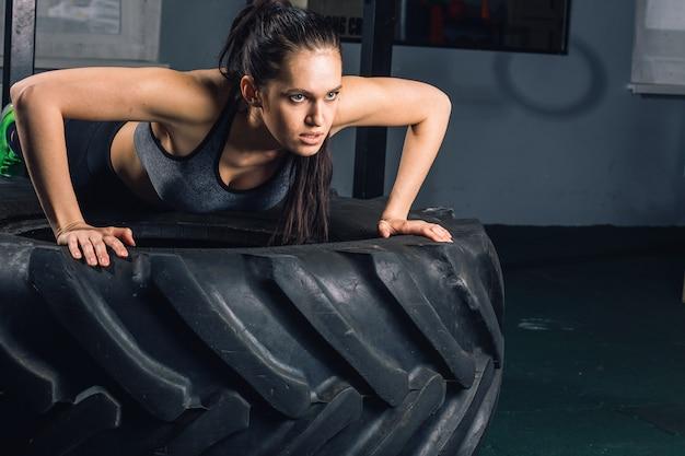 プッシュを行うスポーティな女性に合わせてタイヤ強度パワートレーニングコンセプトにups