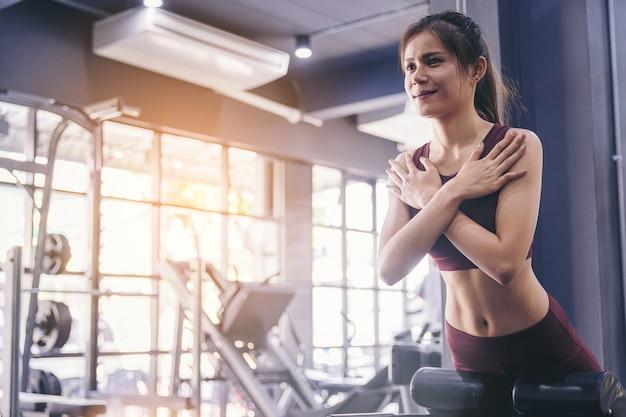 座っている若い女性は、フィットネスジムでマシンでups運動します。腹筋と平らな腹のための女性のトレーニング。