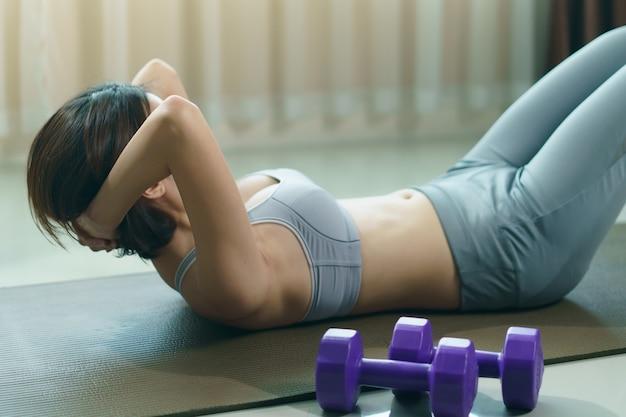 自宅で灰色のスポーツウェアの運動で若い女性、腹筋座るups
