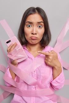 화난 중독된 갈색 머리 아시아 여성은 스마트폰에서 기술 중독 포인트를 피하기 위해 벽에 칠한 것처럼 전화를 사용할 수 없습니다.