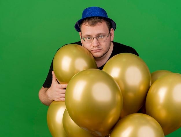 Расстроенный взрослый славянский мужчина в оптических очках в синей праздничной шляпе держит гелиевые шары