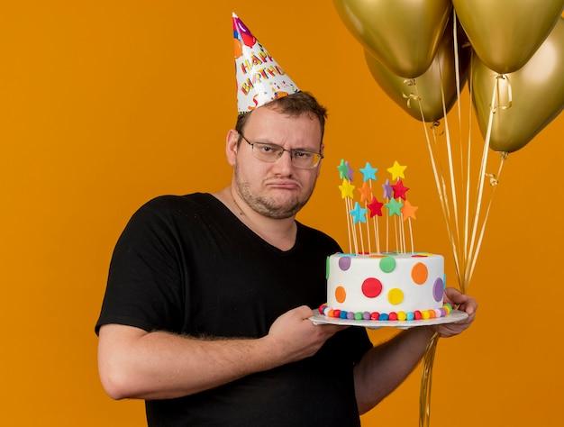 Upset adult slavic man in optical glasses wearing birthday cap holds helium balloons and birthday cake