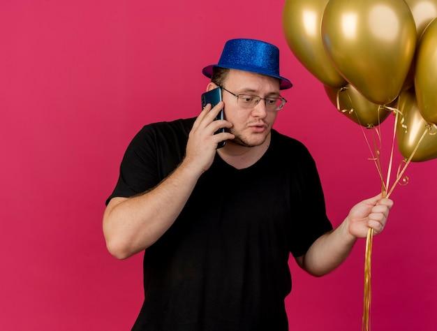 Sconvolto uomo slavo adulto in occhiali ottici che indossa un cappello da festa blu tiene palloncini di elio che parlano al telefono