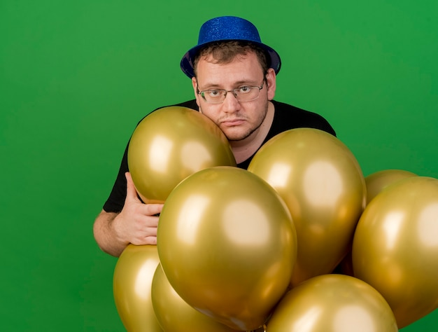Upset adult slavic man in optical glasses wearing blue party hat holds helium balloons