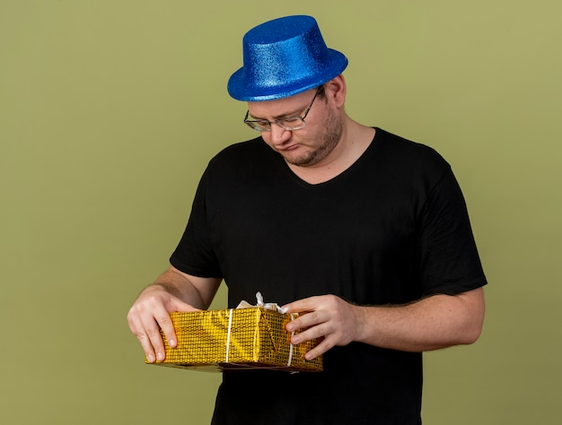 Upset adult slavic man in optical glasses wearing blue party hat holds and looks at gift box