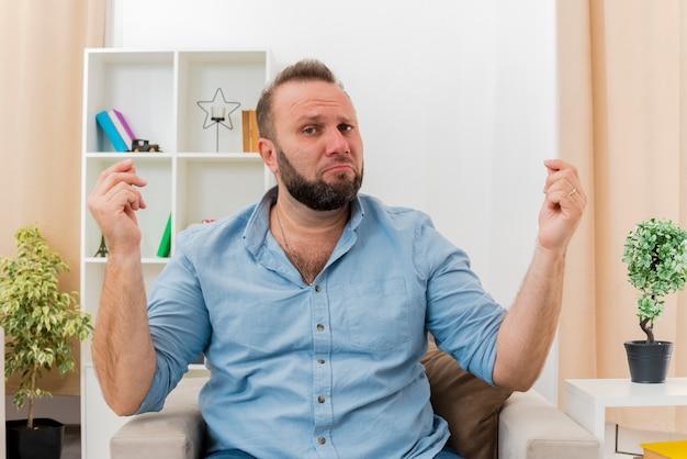 Расстроенный взрослый славянский мужчина сидит на кресле, жестикулируя знак рукой деньги двумя руками, глядя в камеру внутри гостиной