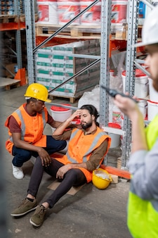 Upset african-american guy in yellow hardhat supporting colleague who sitting on floor and massaging forehead because of headache