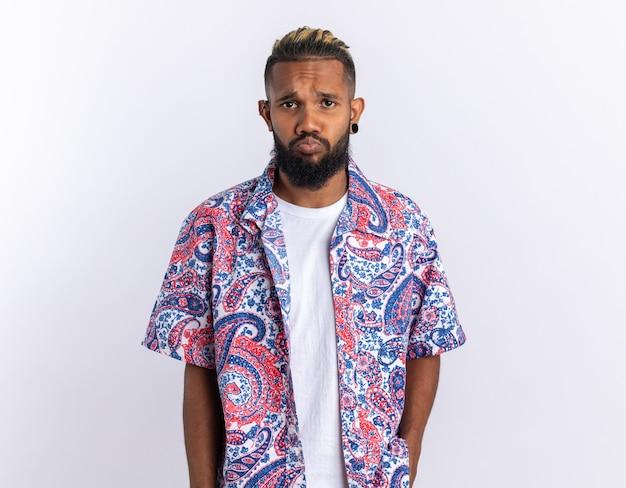 Sconvolto giovane afroamericano in camicia colorata guardando la telecamera con espressione triste in piedi su sfondo bianco