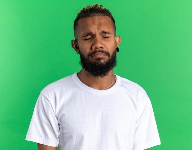 Sconvolto giovane afroamericano in maglietta bianca con espressione triste che increspa le labbra con gli occhi chiusi