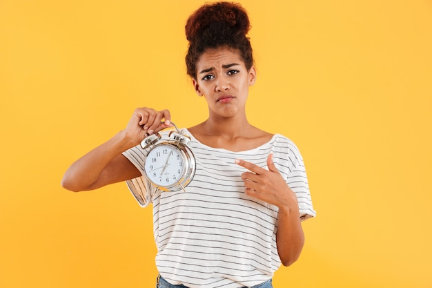 Upset african woman holding alarm clock and pointing on them