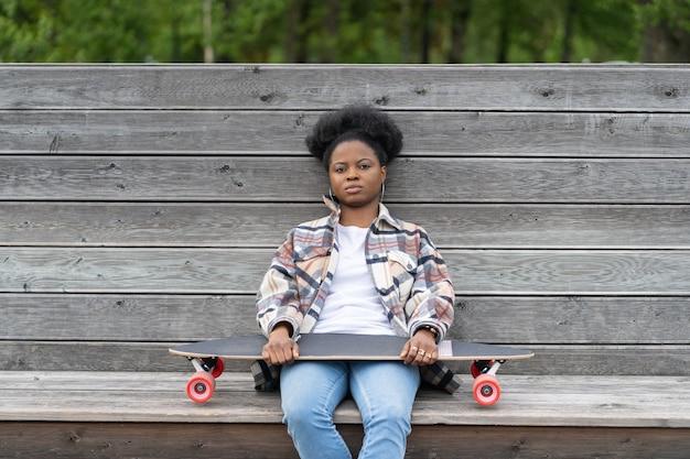 疲れているか落ち込んでいる動揺したアフリカの女性は、都市空間だけでロングボードとベンチに無関心に座っています