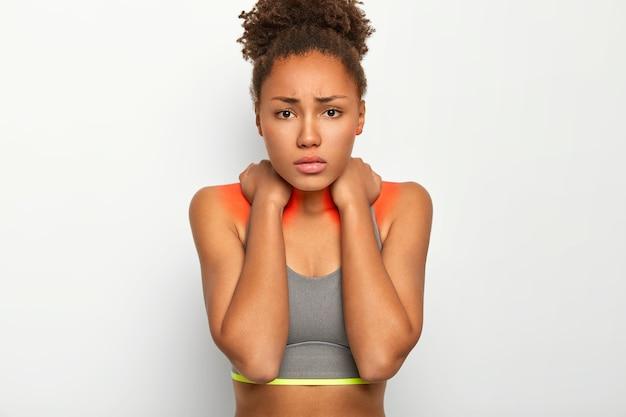 動揺したアフロの女性は首の痛みに苦しんでおり、悲しくて不快に見え、炎症を起こしたゾーンを示し、カジュアルなトップに身を包み、肌が黒くなっています