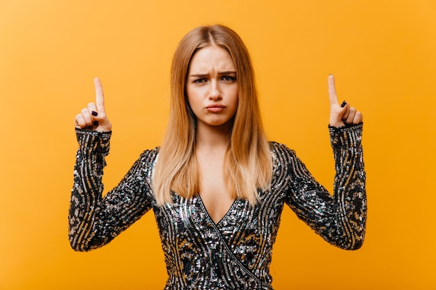 Upset amazing woman in party attire posing with hands up. portrait of pretty fair-haired woman.