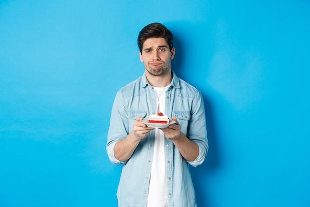 Расстроенный и мрачный мужчина держит праздничный торт, надувается и печально стоит у синей стены