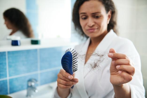 빗으로 빗질 후 머리카락이 떨어지는 것을 보고 욕실에서 화나고 충격을 받은 여성