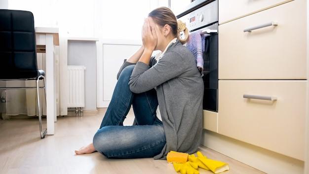 台所の床に座って泣いている動揺してストレスを感じている若い女性。