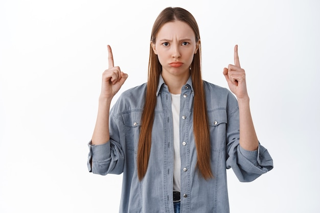 Upset or angry girl frowning, sulking and pointing fingers up at bad thing, being jealous, want something, complaining, standing disappointed against white wall
